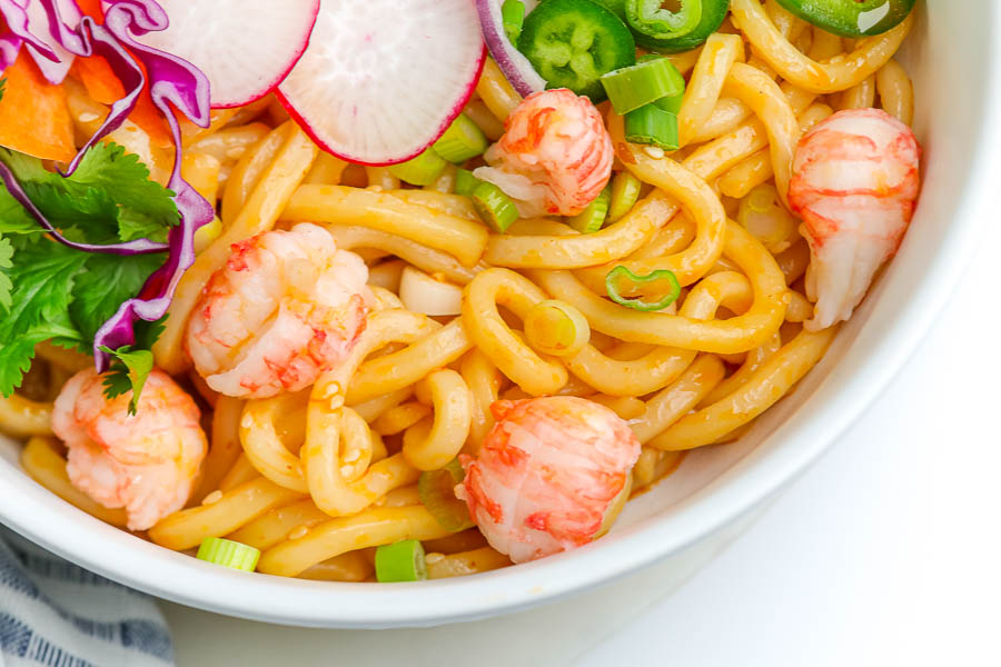 asian noodles in a white bowl with slices of radish and red cabbage
