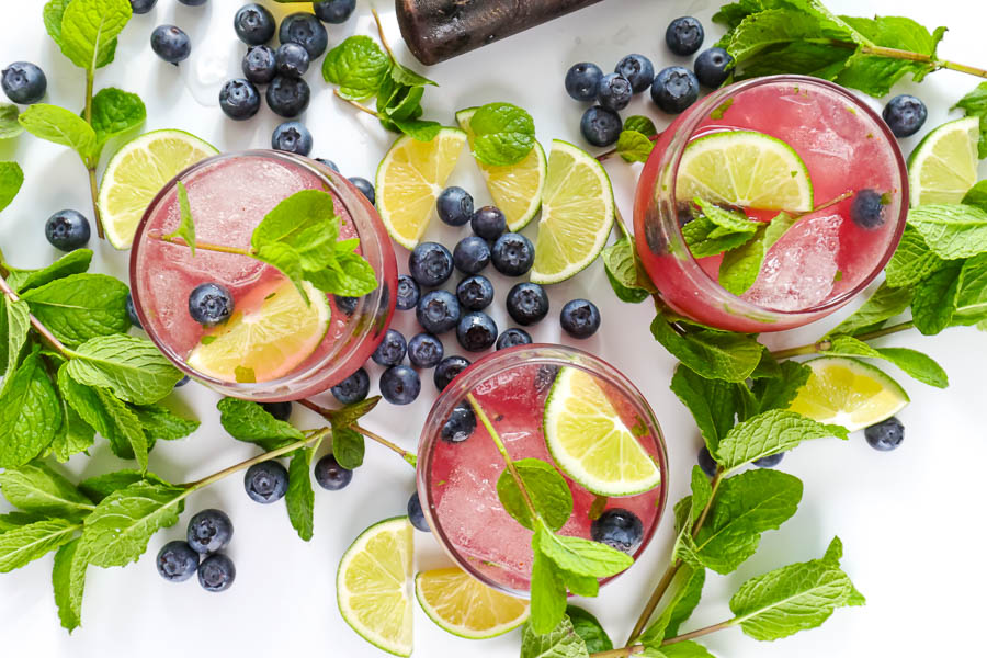 three glasses of mint mojito on a white background with fresh fruit