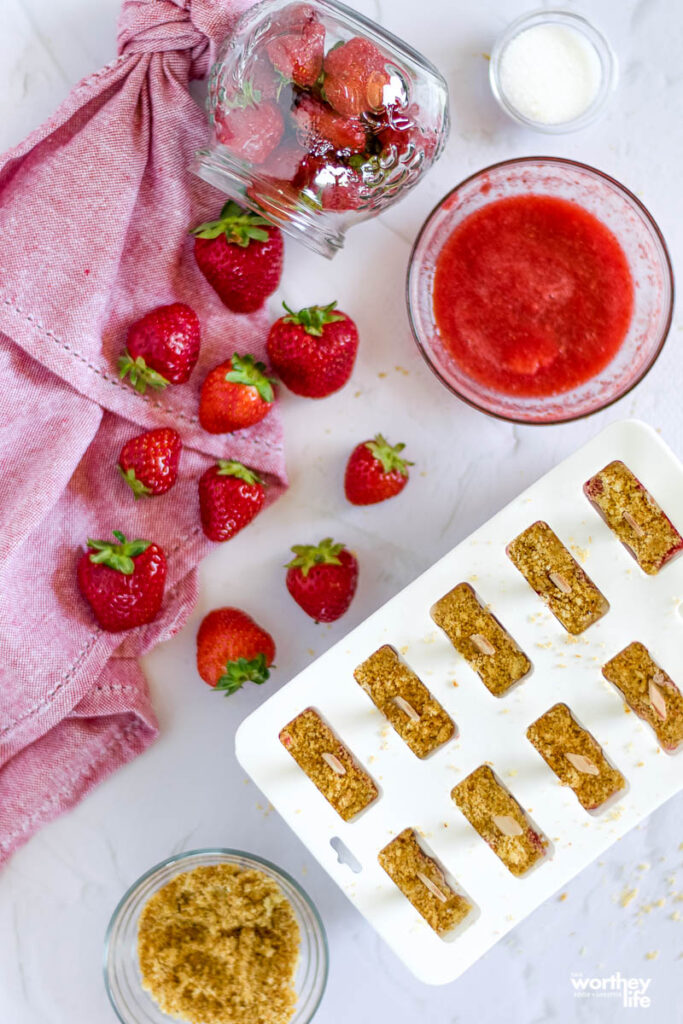 the making of Strawberry + Coconut Milk Crumble Popsicles on a white background