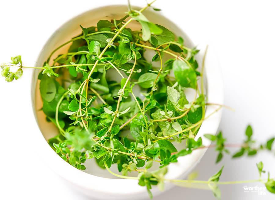 fresh herbs in a white bowl
