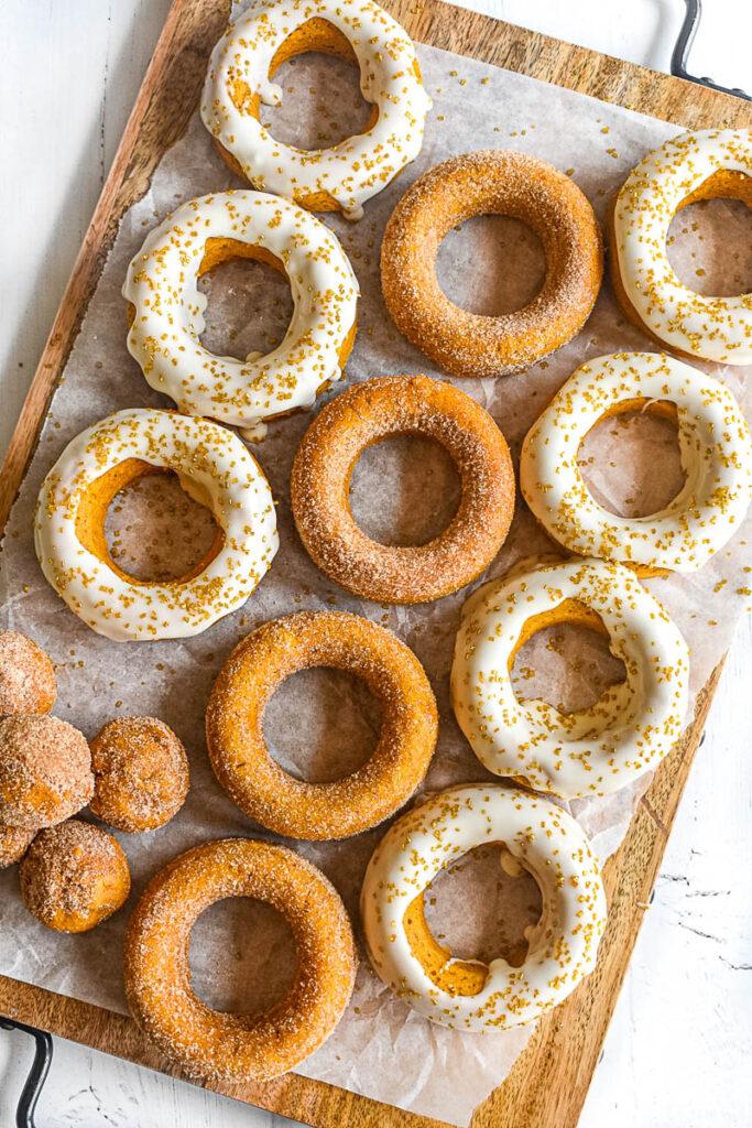 pumpkin donut holes on baking sheet with doughnuts