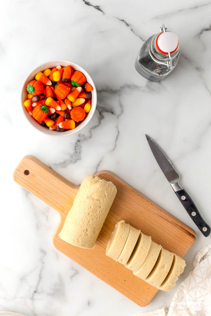 slicing cookie dough on cutting board