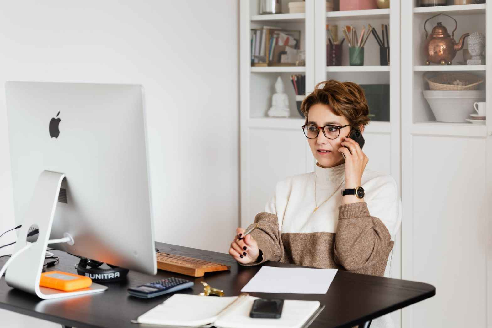 serious female executive communicating on mobile phone in cozy office