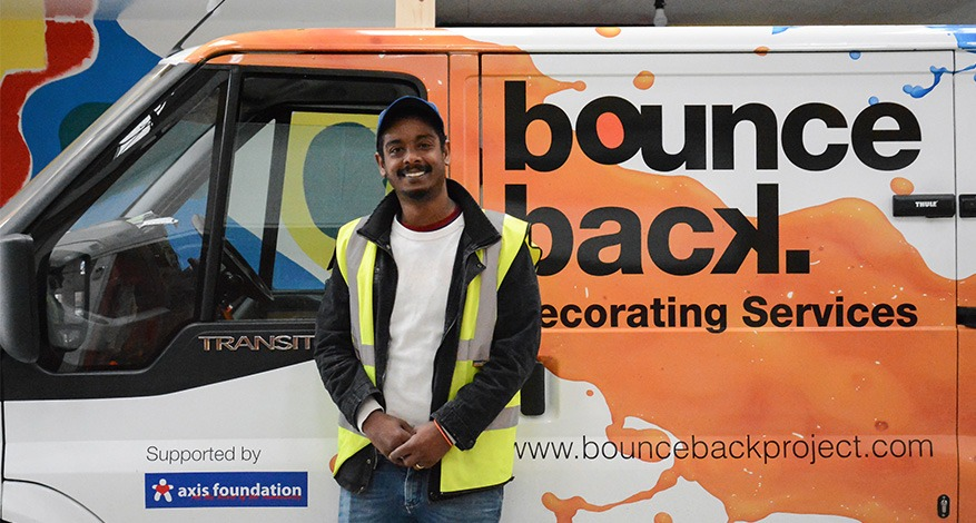 A painter and decorator stood beside branded Bounce Back van.
