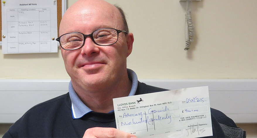 Man holding donation cheque for Singing group