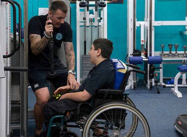 Man and boy at gym in adaptive sports centre