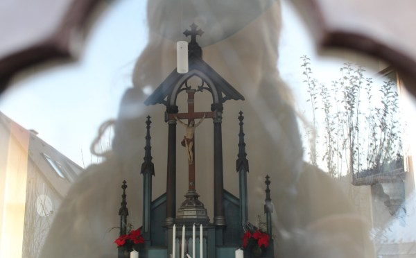 Woman looking at Christian Altar through glass door Mala Skala North Bohemia