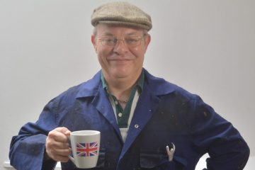 An elderly gentleman looks at the camera smiling, with a cup of tea in his hand