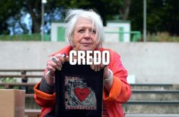 An elderly woman holds a frame with a heart in it and is looking at the camera. Credo is written across the screen
