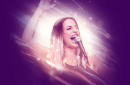 A woman is singing into a microphone against a purple backdrop.