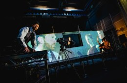 Man crouches in front of projections of a man, woman and puppet on a large trailer.