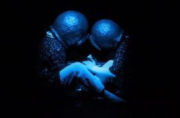Two people with metal bowls on their heads sit on the ground, light in blue light.