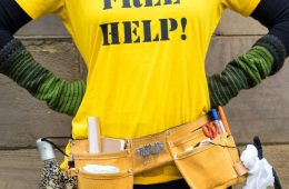 "A person with their head cropped out of shot stands with their hands on their hips, wearing a bright yellow t-shirt which says ""FREE HELP!"" on it in black letters and a workbelt full of tools worn on their hips."
