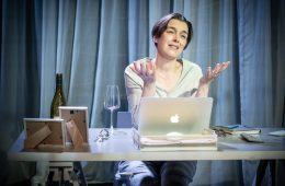 A woman is sitting at a desk with a laptop and a wineglass in front of her.