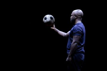 A man standing alone on stage, balancing a football on one hand.