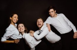 Four young white people stand against a black backdrop, all wearing matching white shirts. The one on the far left stands with her hands on her hips, and the two in the middle lean towards her, smiling and laughing. The one on the far right rests his right arm on the others.