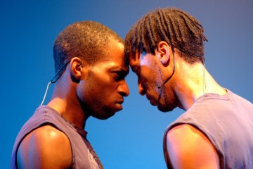 Two black men, forehead to forehead, looking serious on a blue background