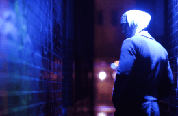 Blue light, a hooded figure has his back to us, but turns his head looking over his shoulder