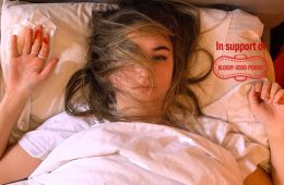 A young woman is lying on her back in bed. Her hair is in a halo around her head and one of her hands has blood stains on it.