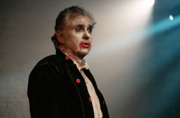 A man standing on stage with a spotlight on him. His face is covered with clown makeup.