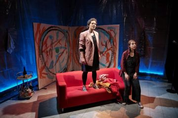 Two women, one standing on a red sofa and one on the floor.