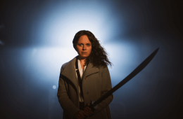 A woman holding a sword stands in front of a bright white light.