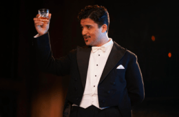 Man in suit raising a glass