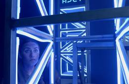 A young woman is peering at the camera through some illuminated scaffolding.