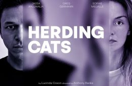"""Portrait of two individuals, standing side by side. Printed in All Capitals across half their aces: """"Herding Cats"""""""