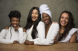 Four black women look at the camera smiling happily.