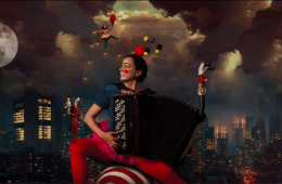 Woman plays the accordion sitting on a ball in front of a cityscape filled with circus performers