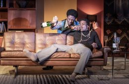 Two Black men dressed in 70s fashion laughing on a sofa