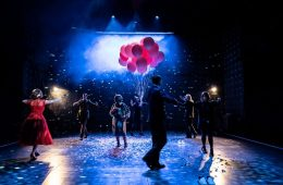 Ensemble on the dark stage with pink balloons