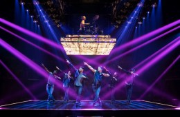 Six men stand in a V formation on stage, blue and purple strobe light on them.