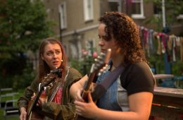 Two women playing guitar. One looks in interest at the other.