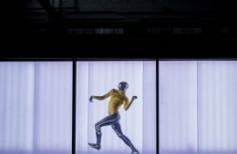 A dancer in futuristic clothes poses in a similarly futuristic background, a thin horizontal strip of lights.