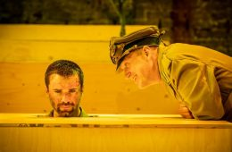 A man sticks his head up out of a box, whilst another man leans over him from the right