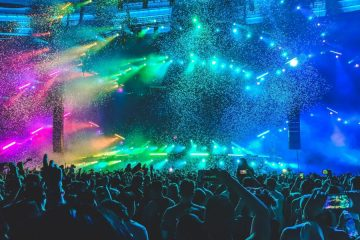 A sea of people at a festival. Strobe lights of every colour dance above them.