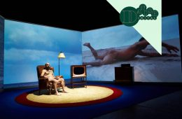 A naked man sits in an armchair in a circular stage, with a television and lamp next to him. An image of the sea is projected onto a screen behind him on the left, whilst on the right is a nude person lying on the sand.