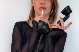 A woman faces us, holding a lollipop in one hand and a telephone in the other