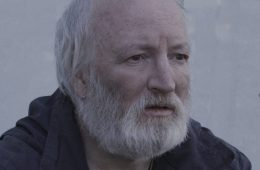 An old man with a white beard stares off into the distance