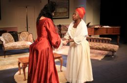 An actor in a red dress holds the hands of another actor in a white robe and red headscarf