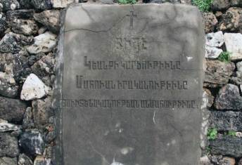 A memorial stone marking over 30 graves buried at the cemetery, which includes the remains of genocide survivors.
