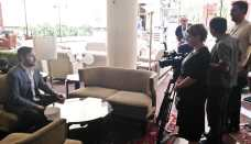 Director Christopher Chambers answering questions during a television interview at the Royal Tulip Grand Hotel.