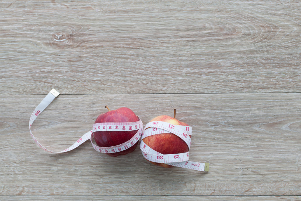 Red apple  and measuring tape.The concept of weight control Lose Weight With Fruit,  Diet concept, Adverse effects of excessive weight loss.