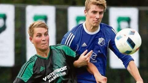 Mit eingehakten Armen kämpfen der Emmendorfer Luca Schenk (links) und Bodenteichs Frederik Strauß um den Ball.