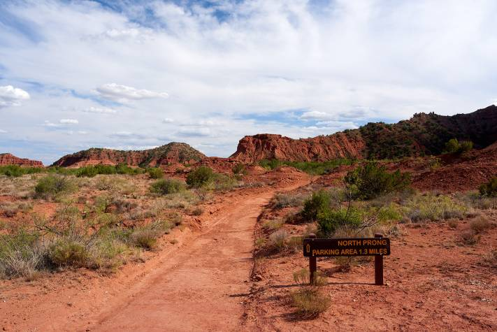 Red sandstone cliffs and interesting clouds along a trail at Caprock Canyon State Park.