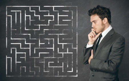 shows business man in front of a confusing maze