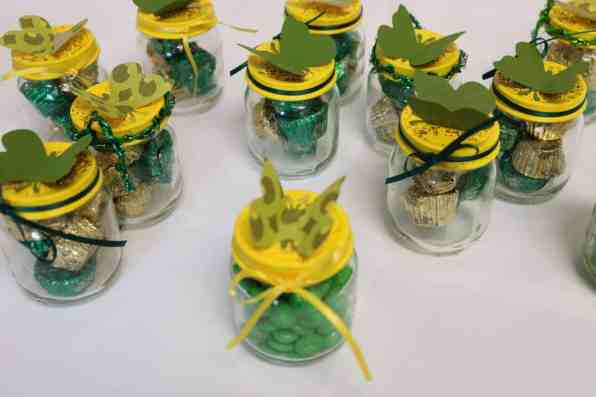 jars with butterflies on lids, ribbons, and candy in the jars https://www.b4andafters.com/Baby-Shower-Favors