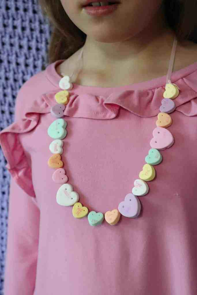 Candy Heart Necklace being worn by girl wearing a pink shirt https://www.b4andafters.com/conversation-heart-necklace